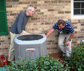 Buddy De Lozier (right), of Central, inspects a new heat pump with a homeowner participating in