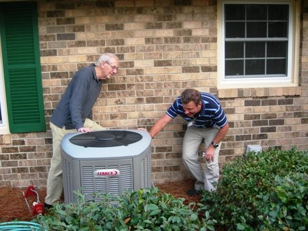 Buddy De Lozier (right), of Central, inspects a new heat pump with a homeowner participating in the pilot program (Photo credit: ECSC)