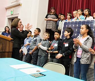 Oregon Gov. Kate Brown during the bill's signing ceremony at a Portland elementary school powered by solar panels (photo courtesy of the Governor's Office).