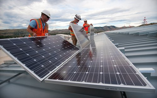 Installing solar panels on the roof of a research facility. Courtesy of DOE/NREL